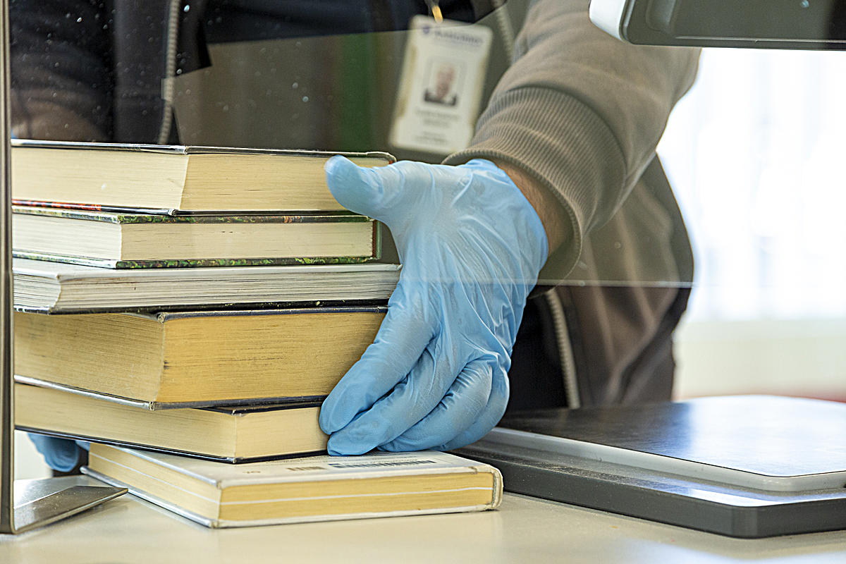 Returned library books handled with rubber gloves